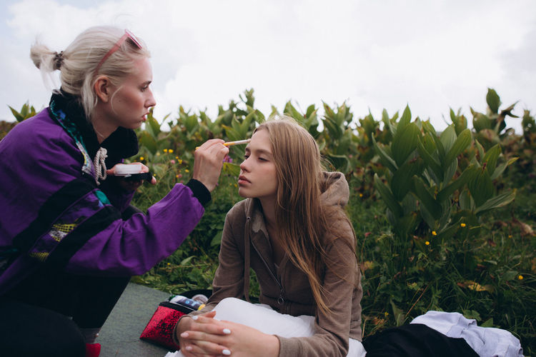 Young woman doing make-up on friend sitting on grass against sky