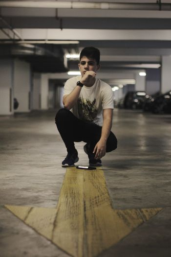 Portrait of young man crouching in parking lot