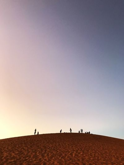 Group of people on desert against clear sky