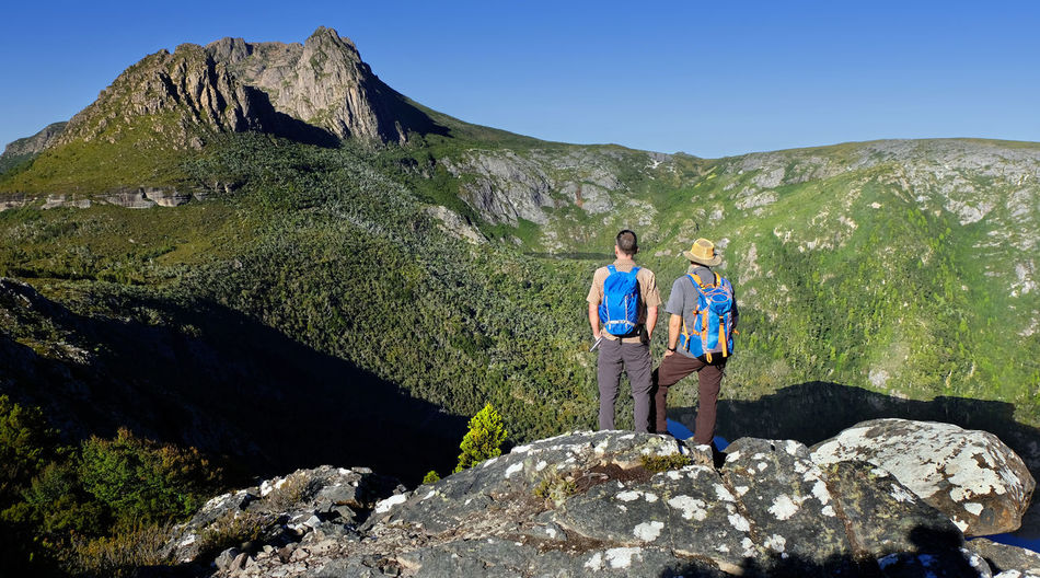 Rear view of male hikers standing against mountains