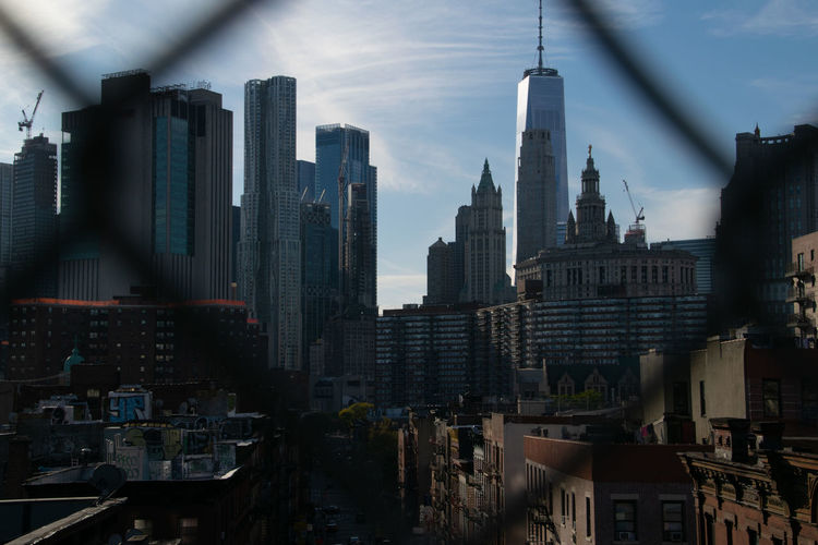 Buildings in city seen through chain link fence