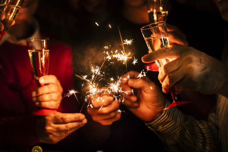 Midsection of friends holding sparklers and champagne at night