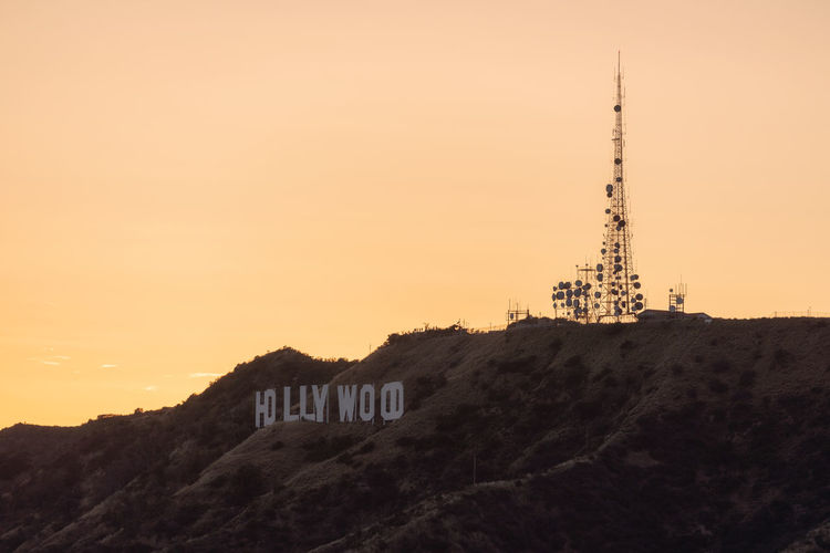 Hollywood sign at sunset, Los Angeles Built Structure Sky Sunset Mountain Tower No People Connection Communication Beauty In Nature Tourism Tranquil Scene Travel Scenics - Nature Hollywood Sign Hollywood Antenna Communications Tower Los Angeles, California The Traveler - 2019 EyeEm Awards