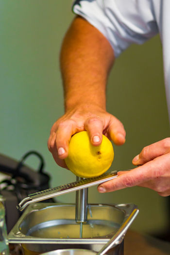 Cropped hands of man grating lemon