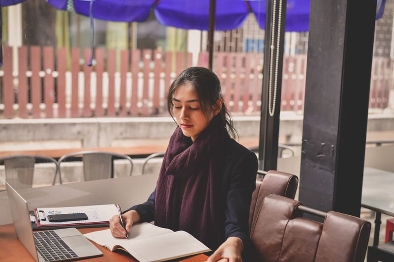 Sitting Real People One Person Focus On Foreground Casual Clothing Table Publication Communication Young Adult Wireless Technology Front View Book Young Women Lifestyles Technology Connection Holding Portrait Using Laptop Beautiful Woman