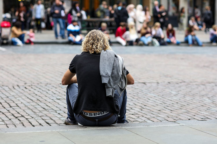 Rear view of young man sitting on footpath on crowded street