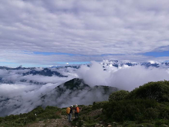 Rear view of hikers standing on mountain against cloudy sky