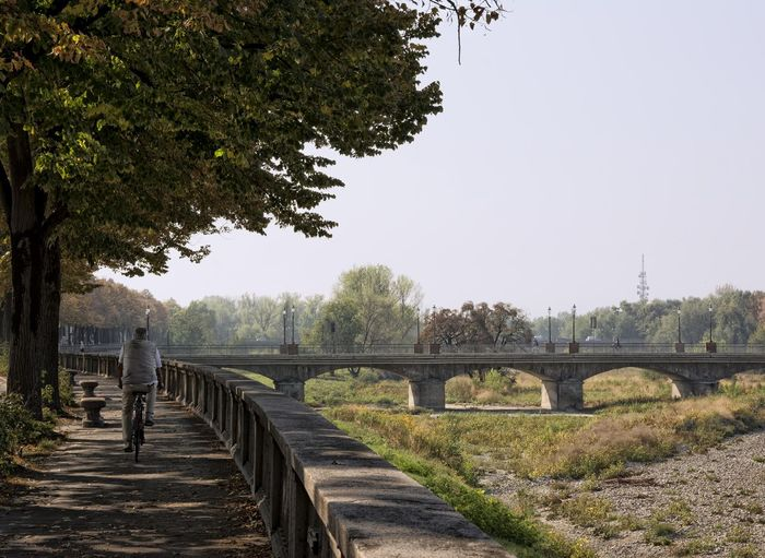 Rear Of Man Cycling On Footpath Against View Of Bridge