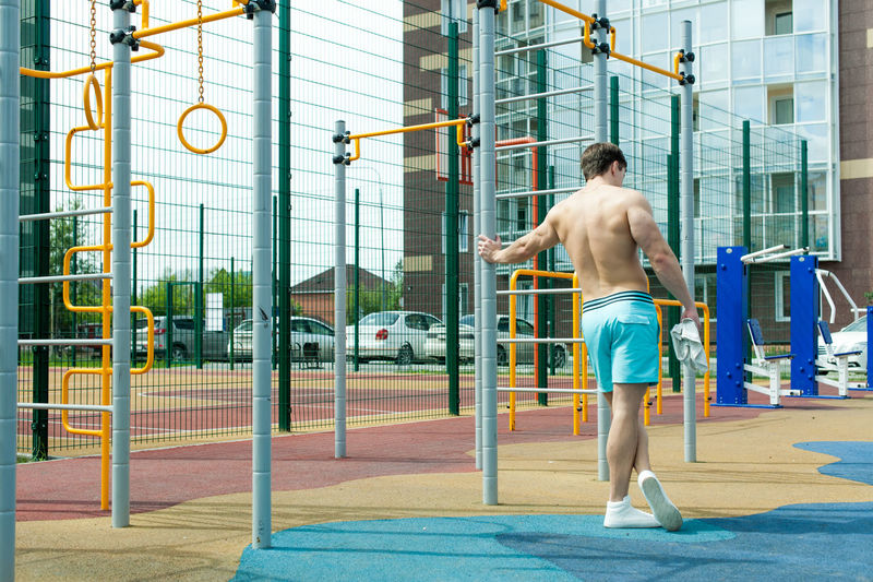 Rear view of shirtless man standing by gymnastics equipment against building