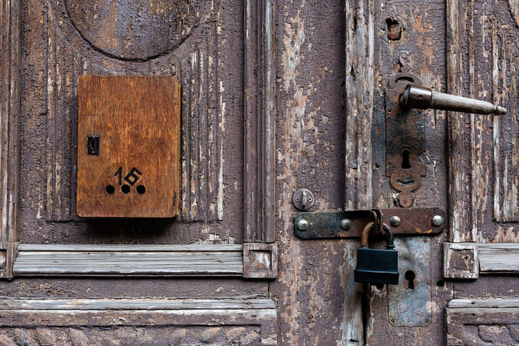 Old wooden door with damaged color and mailbox. Door Entrance Wood - Material Old Metal Lock Closed Protection Safety Security No People Latch Close-up Rusty Day Full Frame Backgrounds Handle Weathered Damaged Color Postbox Padlock