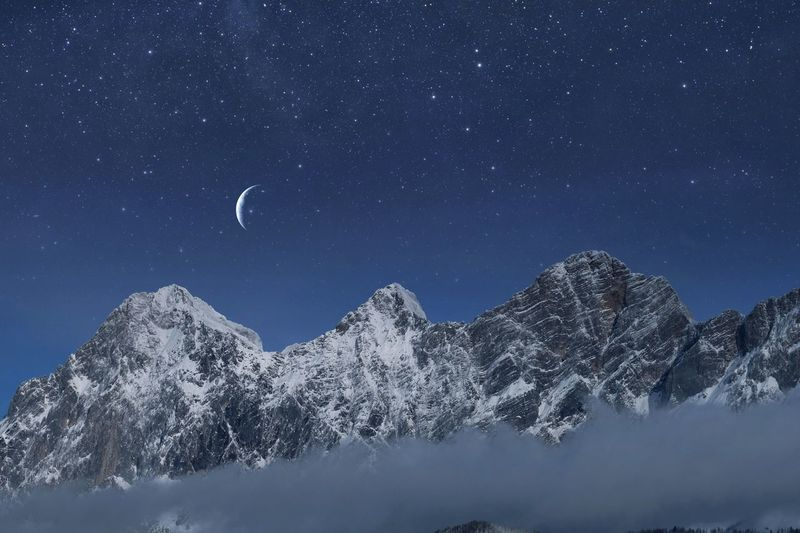 Low Angle View Of Snowcapped Mountains Against Sky At Night