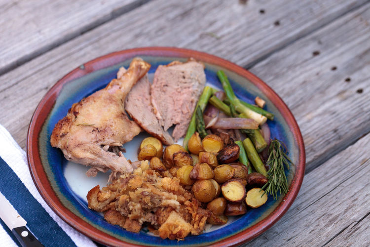High angle view of roast chicken with vegetables served in plate on wooden table
