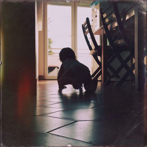 Rear view of baby crawling on floor at home