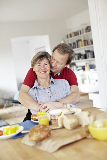 Portrait of smiling woman having food at home