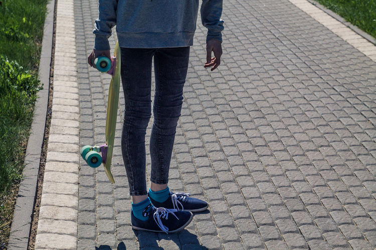 Low Section Of Woman With Skateboard Standing On Footpath
