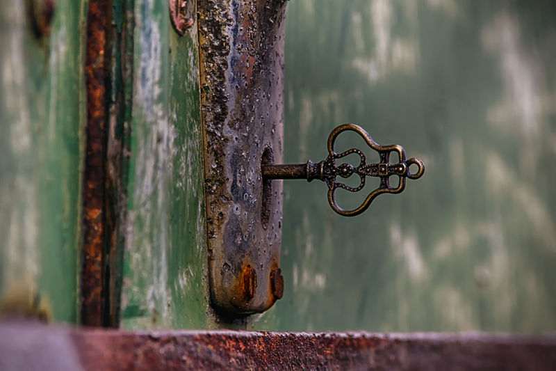 Close-up of key in hole of rusty door