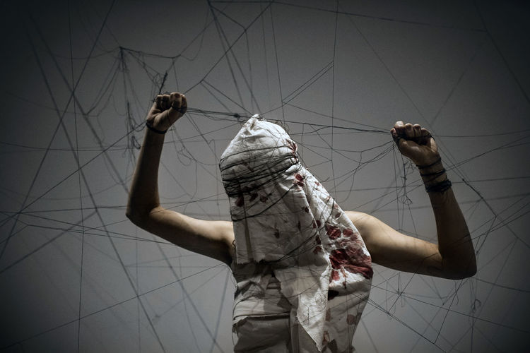Woman tangled in strings covered with blood stained fabric standing against gray background