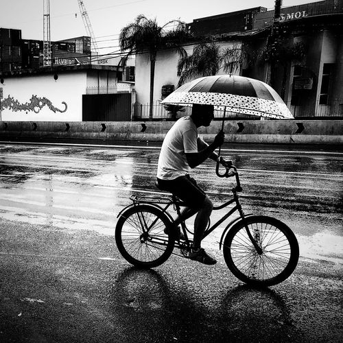 Man with bicycle on wet street