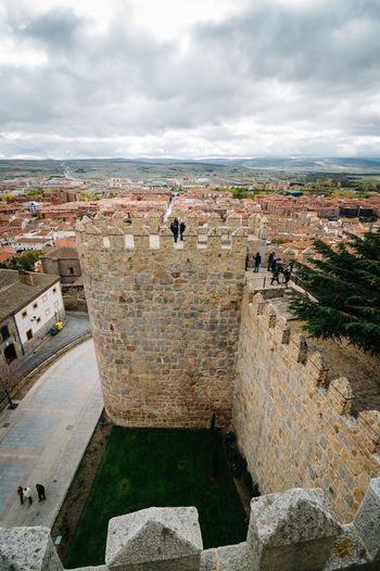 People at walls of avila against cloudy sky
