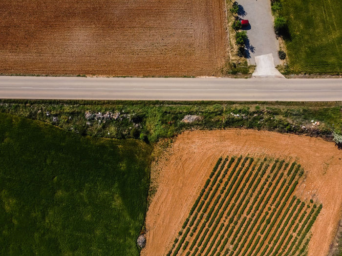 Aerial top drone view of road amidst farmland