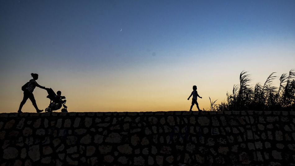 baby stroller Clear Sky Copy Space Full Length Group Of People Land Lifestyles Nature Outdoors Real People Silhouette Sky Stone Wall Sunset Togetherness