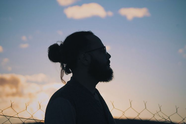 Portrait of silhouette bearded mn standing against sky during sunset