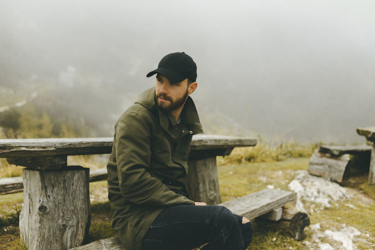 Man looking away while sitting on wooden bench Lifestyle Nature Baseball Cap Casual Clothing Day Focus On Foreground Fog Foggy Morning Julian Alps Leisure Activity Lifestyles Nature One Person Outdoors Real People Sitting Sky Three Quarter Length Young Adult Young Men