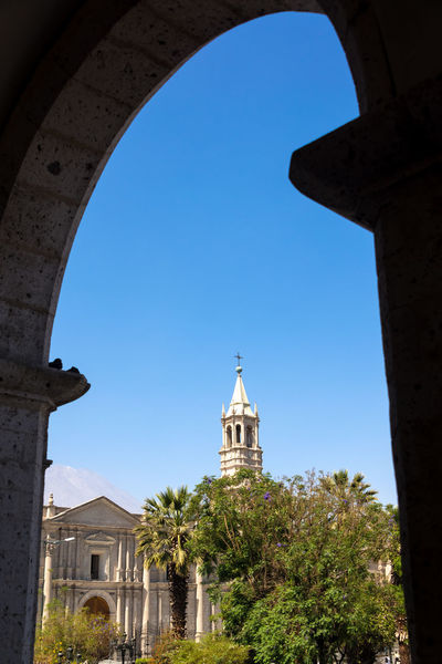 View of the cathedral of Arequipa, Peru framed by the arch of a nearby building Andes Arch Architecture Arequipa Cathedral Catholic Catholicism Church Church City Colonial Colonial Architecture Historic Landmark Peru Plaza Plaza De Armas Sillar South America Stone Travel Destinations