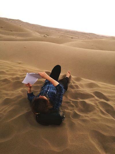 Man relaxing on sand in desert