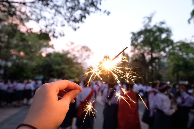 Cropped hand holding lit sparkler with crowd on road in city during sunset