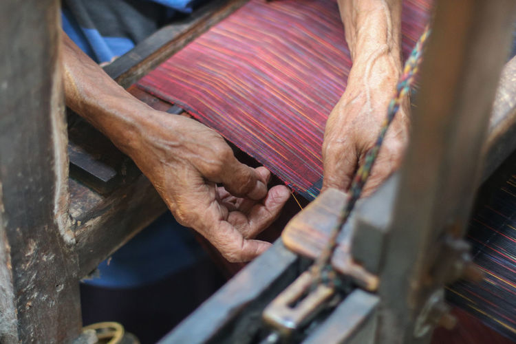 Cropped hands of senior person working at textile industry