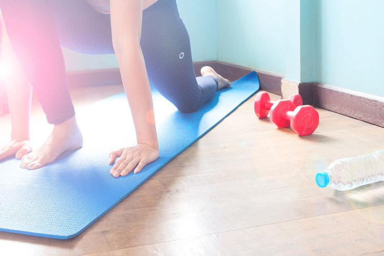 Low Section Of Woman Exercising While Sitting On Exercise Mat In Gym