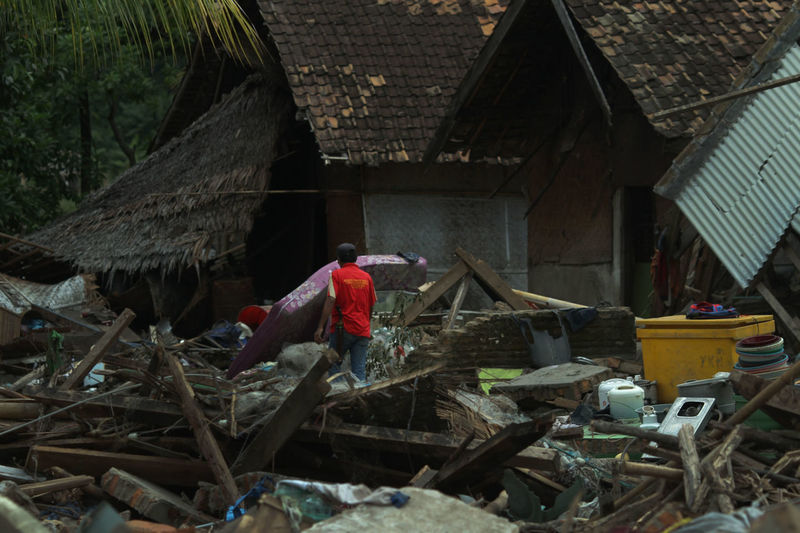 Tsunami Aftermath in Lampung, Indonesia Working Real People Occupation Built Structure One Person Architecture Building Men Day Nature House Building Exterior Full Length Wood - Material Clothing Roof Outdoors Hut Lifestyles Tsunami Tsunami Disaster Lampung South Lampung INDONESIA