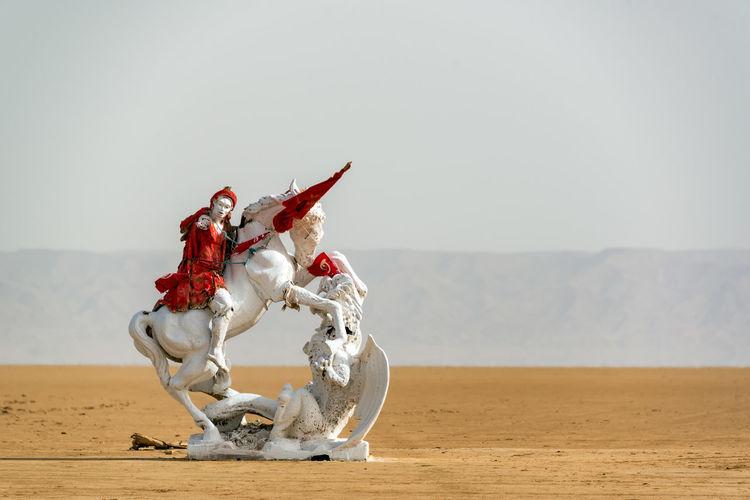 Horse cart on sand against clear sky