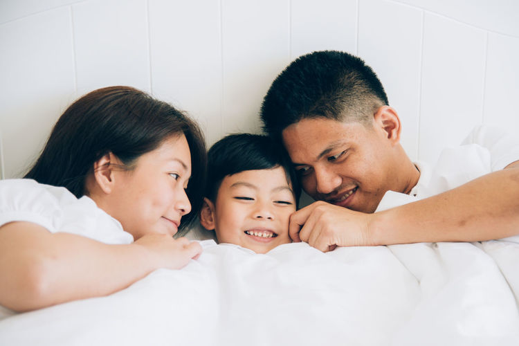 Bed Bonding Boys Child Childhood Daughter Family Furniture Group Of People Headshot Indoors  Innocence Lifestyles Lying Down Males  Men Mother Parent Portrait Positive Emotion Real People Sister Son Togetherness