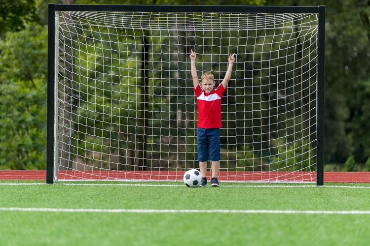 Boy playing soccer ball on field