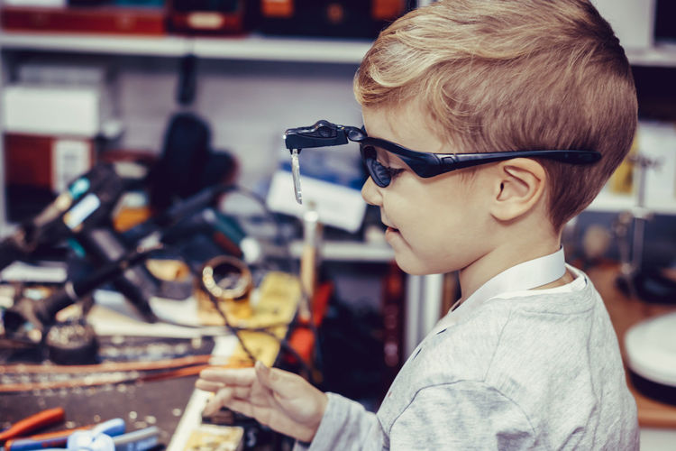 Small boy with magnifying eyeglasses in engineering workshop.