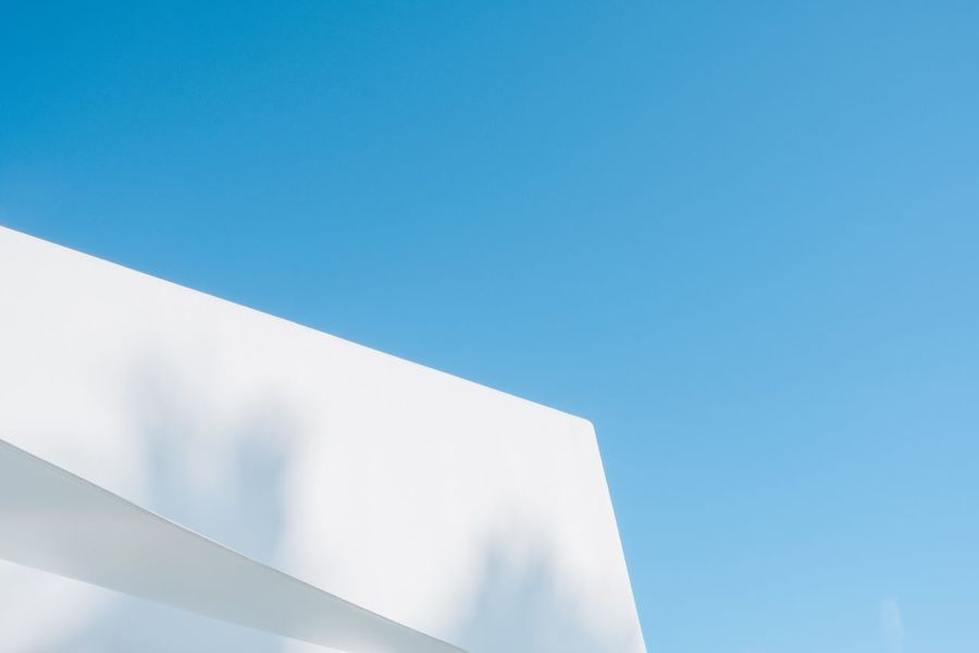 Whitewashed house on blue sky with palm tree shadow White Blue Whitewashed House Shadow Blue Copy Space Architecture Clear Sky Built Structure Low Angle View No People Building Exterior Sky Day Modern