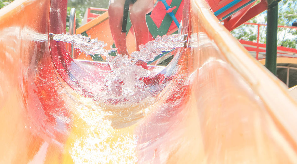 Water splashing in water slide with person in background