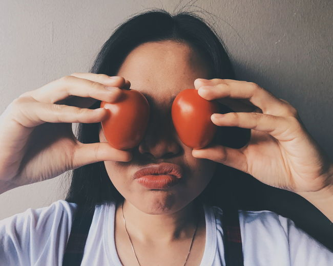 Close-up of woman covering eyes with tomatoes