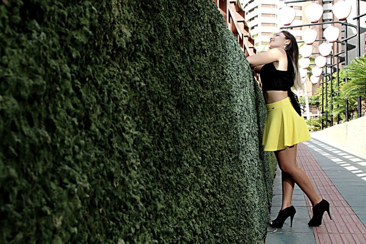 Full Length Of Young Woman Standing By Ivy Covered Wall On Footpath