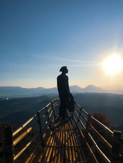 Man standing on mountain against sky during sunrise