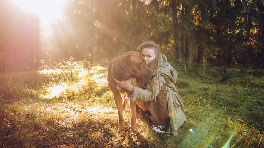 Young smiling woman with dreadlocks in autumn fall forest in the morning sunshine playing with a dog ridgeback Mammal Animal Themes Animal One Animal Pets Domestic Animals Land Domestic Nature Tree Dog Real People Leisure Activity Canine Young Adult One Person Sunlight Vertebrate Forest Lens Flare Warm Clothing Outdoors Dreadlocks Ridgeback