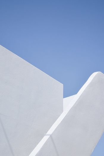 Low angle view of white wall against clear blue sky