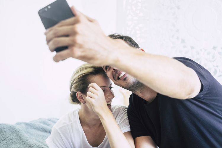 Young beautiful millennial couple caucasian blonde and black hair have fun and laugh taking a selfie or video chat with mobile phone - technology and internet for cute people at home concept - nice lifestyle Two People Adult Women Real People Indoors  Togetherness Lifestyles Men Front View Holding People Communication Mid Adult Young Adult Young Men Casual Clothing Connection Technology Wireless Technology Couple - Relationship Caucasian Back Lit Window Bed Lying Down Side View 20-24 Years 30-34 Years Working Nomadic Laptop Mobile Phone Relaxation