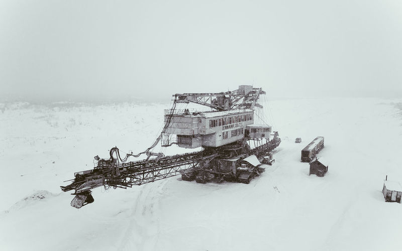 Abandoned boat by sea against sky during winter