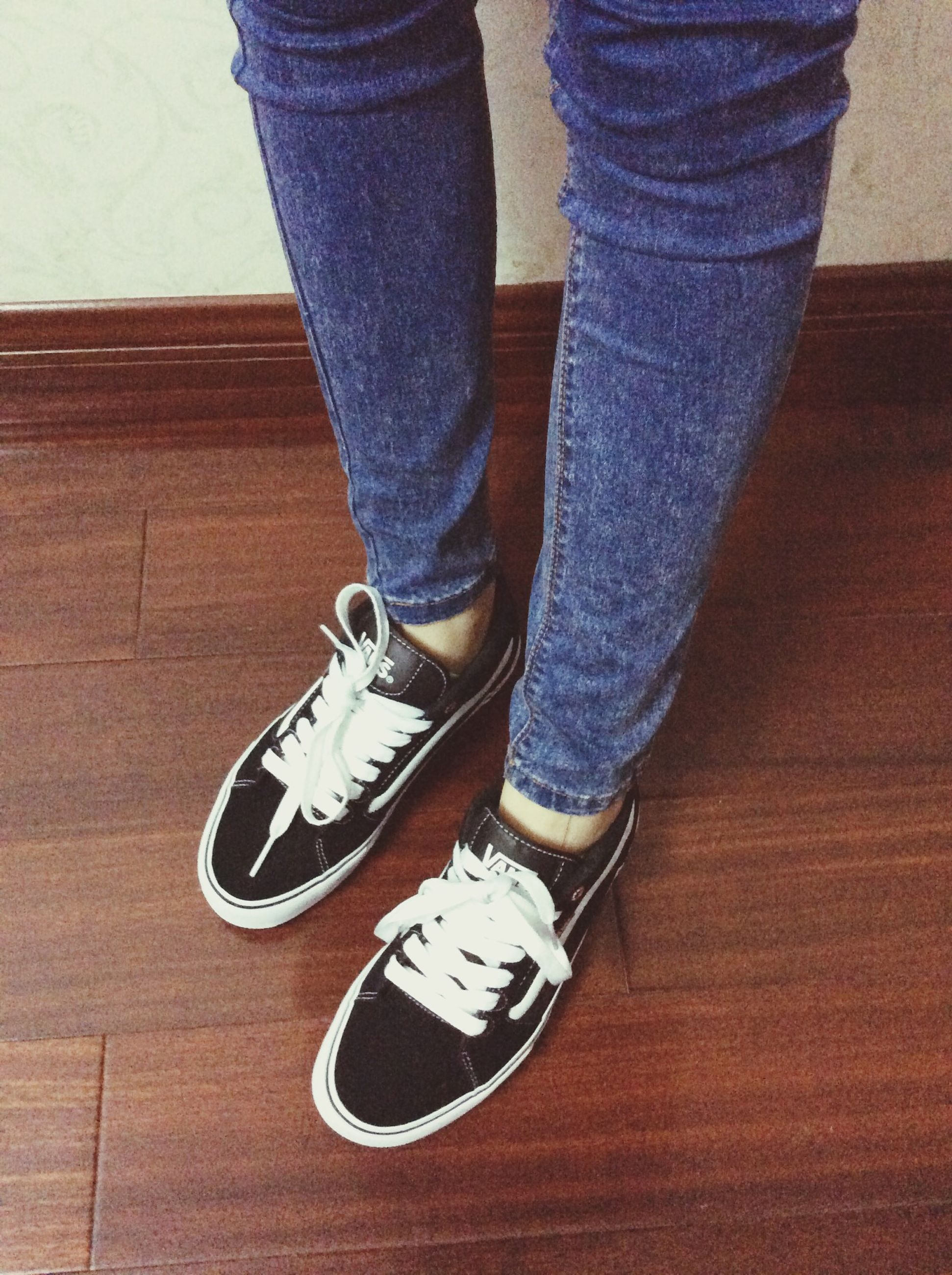 shoe, low section, indoors, person, high angle view, jeans, footwear, casual clothing, lifestyles, standing, wood - material, leisure activity, men, flooring, communication, hardwood floor, sitting