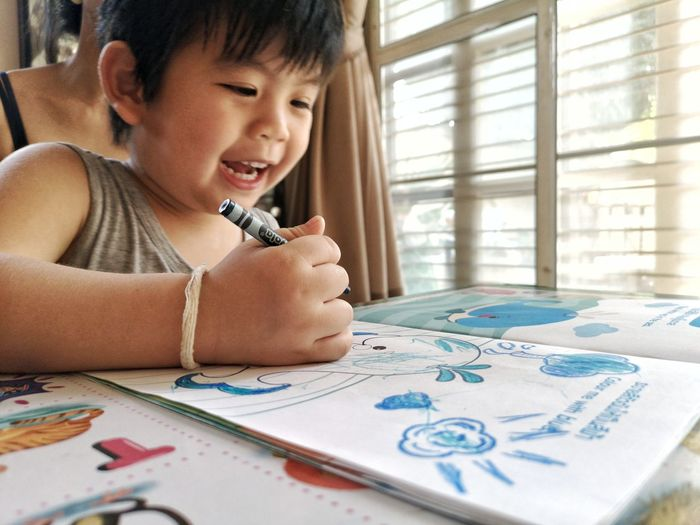 Close-up of smiling boy drawing on book