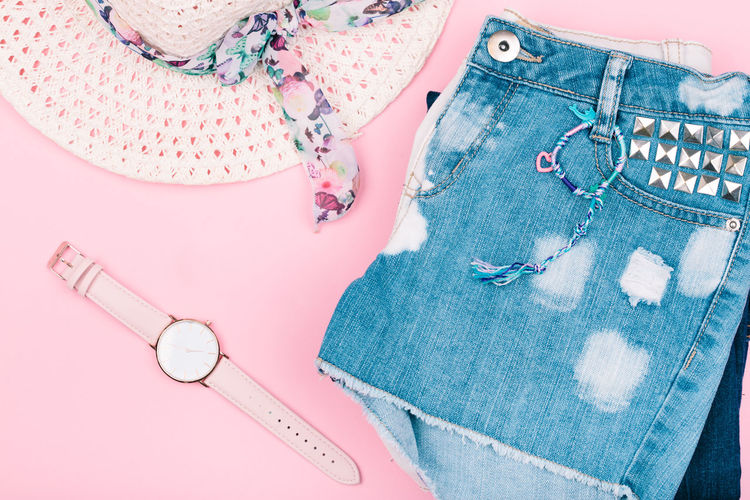 Female girlish clothes, blue jeans shorts, hat, watch on pink background Clothes Summer Summertime Casual Clothing Fashion Girlish Lifestyle Original Style Top View Watch Female Pink Color Bright Hat Denim Jeans Shorts Stylish Above Girl Power