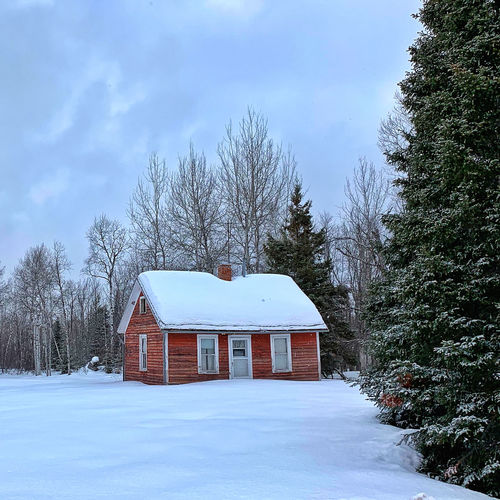 White house on snow covered field by trees against sky